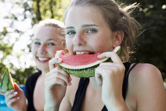 Duas meninas adolescentes comendo fatias de melancia no jardim — Fotografia de Stock