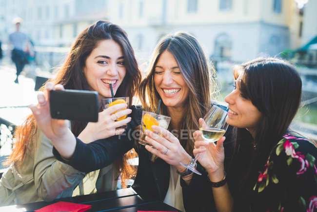 Three women posing for smartphone selfie at waterfront cafe — Stock Photo