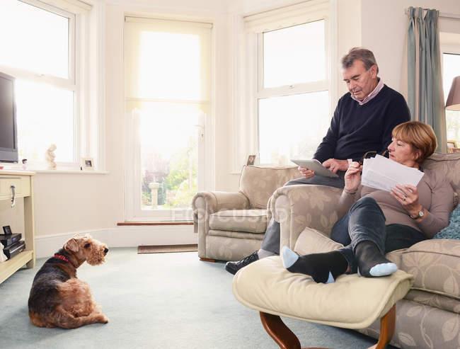 Seniorenpaar schaut sich zu Hause Dokumente und digitales Tablet an — Stockfoto