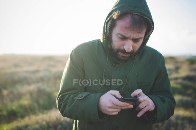 Mid adult man using smartphone whilst chewing matchstick in  field — Stock Photo