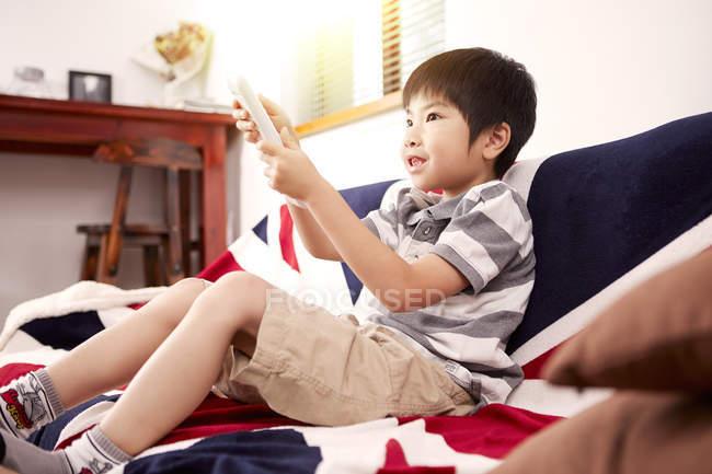 Giovane ragazzo seduto sul divano a guardare la televisione a casa — Foto stock