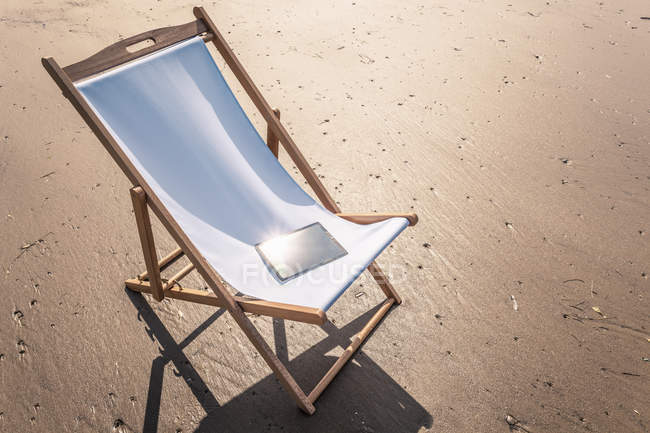 Deck chair on beach with electronic book on seat — Stock Photo