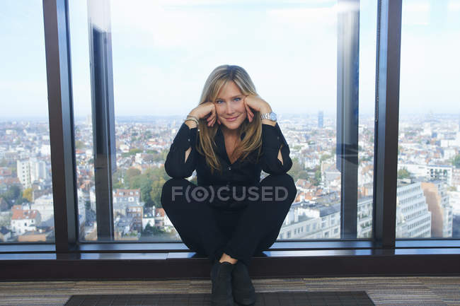 Portrait of confident businesswoman sitting in front of office window with Brussels cityscape, Belgium — Stock Photo