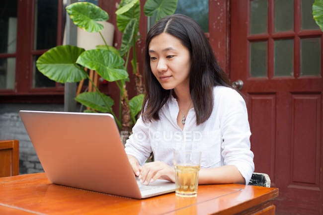 Young Asian woman using laptop outdoors — Stock Photo