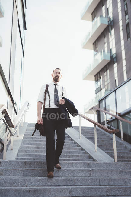 Businessman carrying jacket moving down city stairway — Stock Photo