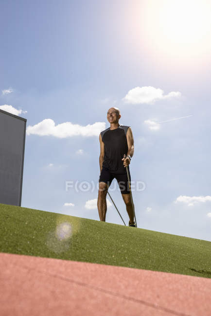 Sportsman walking with hiking pole on field — Stock Photo