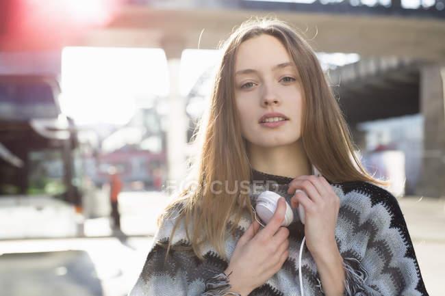 Portrait of beautiful mid adult woman wearing headphones in city — Stock Photo