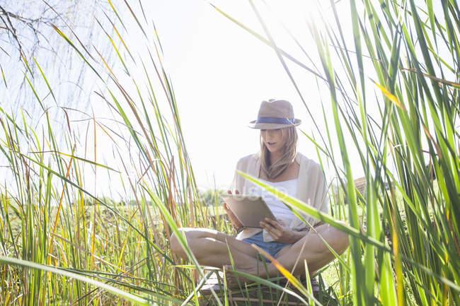 Mulher adulta média sentada em grama longa, usando comprimido digital — Fotografia de Stock