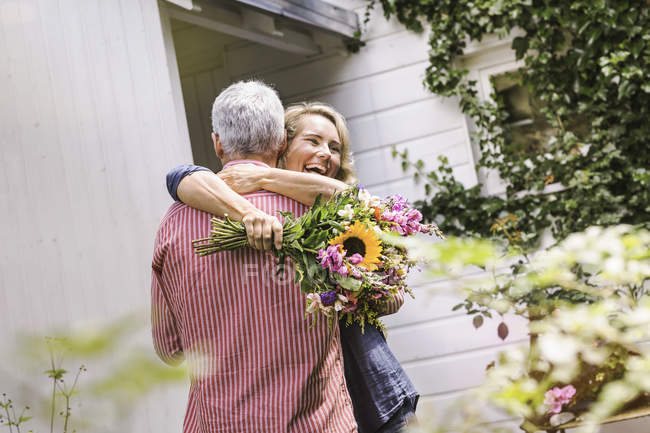 Wife holding bunch of flowers and hugging husband — Stockfoto