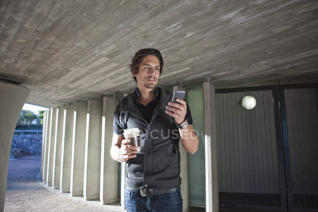 Mid adult man texting on smartphone in city underpass — Stock Photo