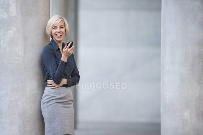 Businesswoman holding smartphone and looking at camera — Stock Photo