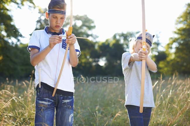 Deux garçons pré-adolescents tenant des arcs et des flèches — Photo de stock