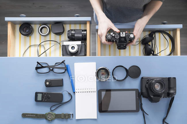 Vista aerea delle mani dei fotografi donne che rimuovono la fotocamera dal cassetto della scrivania in studio — Foto stock