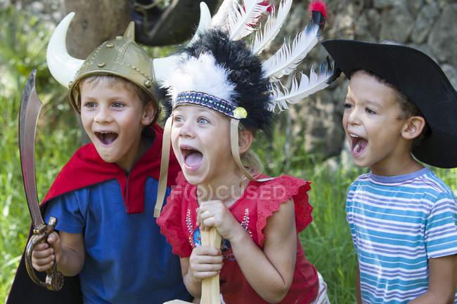 Троє дітей носять модні костюми костюм грати в парку — стокове фото