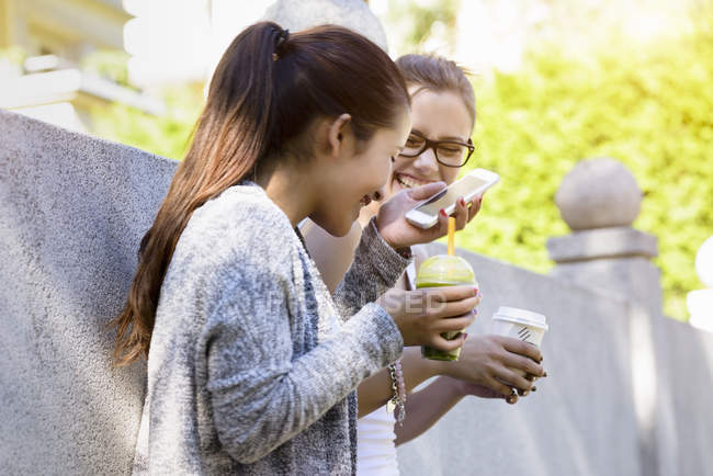 Two young women leaning against park wall laughing and drinking takeaway coffee — Stock Photo