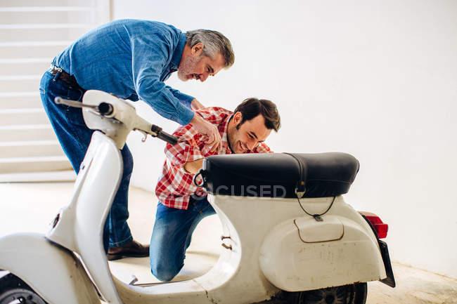 Reifer Mann hilft erwachsenen Sohn zu reparieren moped in garage — Stockfoto