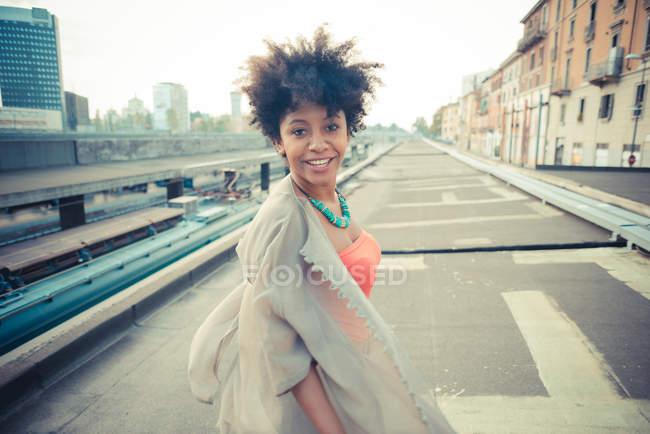 Retrato de uma jovem mulher olhando por cima do ombro na cidade — Fotografia de Stock