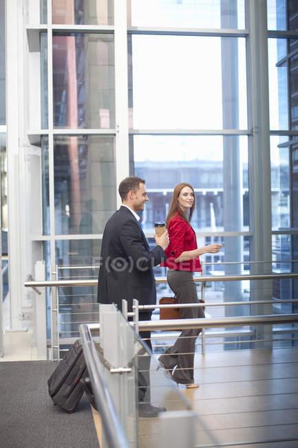 Средняя взрослая бизнес-леди и коллега по дорожке конференц-центра — стоковое фото