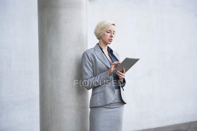 Businesswoman leaning against column, using digital tablet — Stock Photo