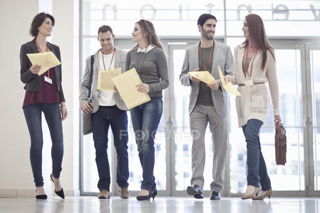 Row of businessmen and women with paperwork in conference centre atrium — Stock Photo