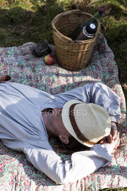 Mulher madura, repousando sobre um cobertor no chão da floresta — Fotografia de Stock