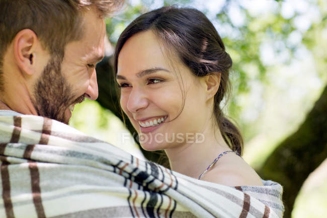 Head and shoulders of young couple wrapped in blanket face to face smiling — Stock Photo