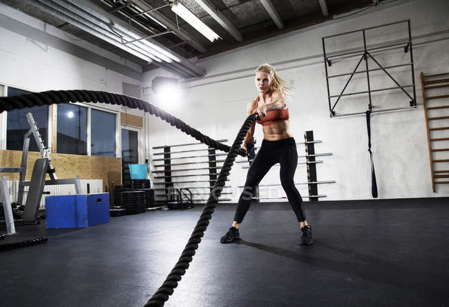 Середині дорослу жінку навчання боротьбу мотузки в тренажерний зал — стокове фото