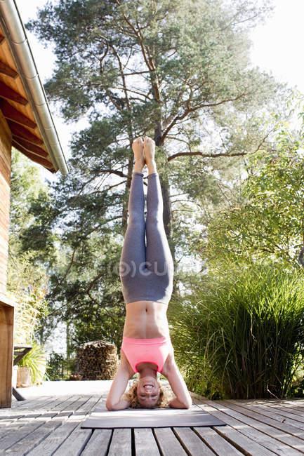 Junge Frau macht Kopfstand im Garten — Stockfoto