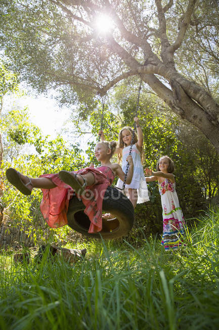 Low angle view of three girls playing on tree tire swing in garden — Stock Photo