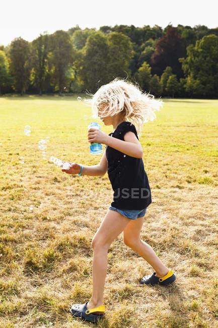 Chica agitando burbuja tubo y hacer burbujas en el Parque - foto de stock