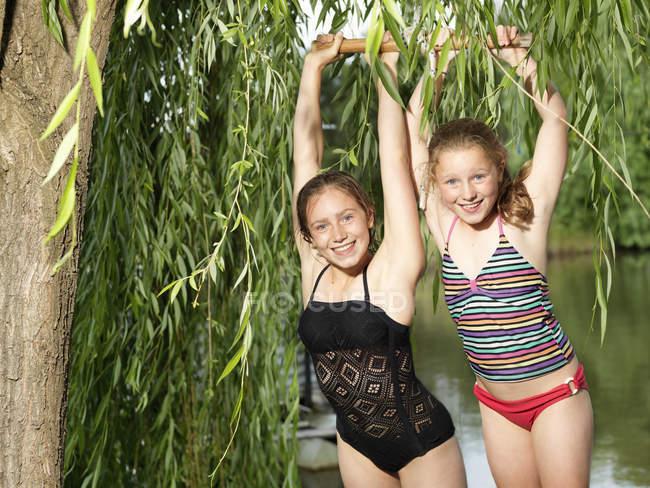 Две сестры висят на качелях у озера. — стоковое фото