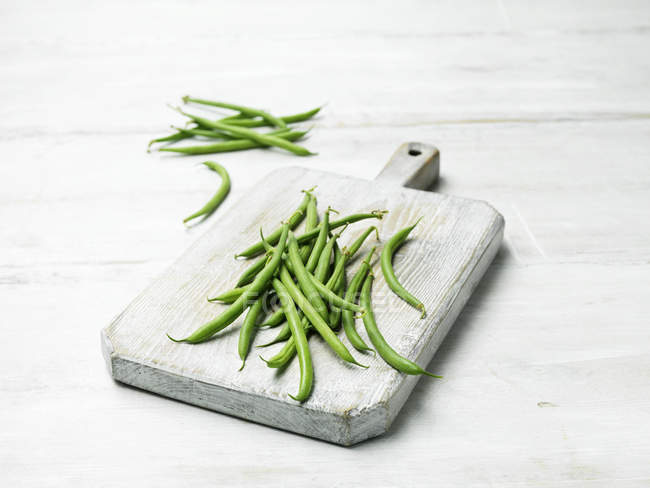 Fresh green beans on wooden chopping board — Stock Photo