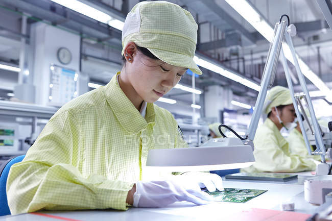 Young woman working at quality check station at factory producing flexible electronic circuit boards. Plant is located in the south of China, in Zhuhai, Guangdong province — Stock Photo