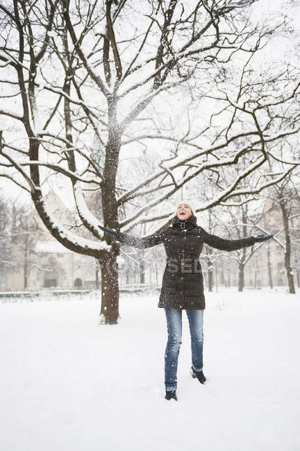 Mid adult woman, arms outstretched, in snow covered rural scene — Stock Photo