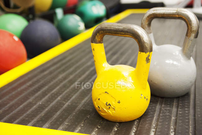 Yellow and grey kettle bells weights in gym — Stock Photo