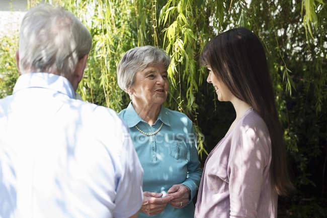 Großeltern und Enkelin unterhalten sich im Garten — Stockfoto