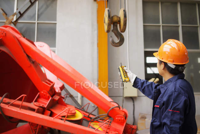 Worker using equipment in crane manufacturing facility, China — Stock Photo