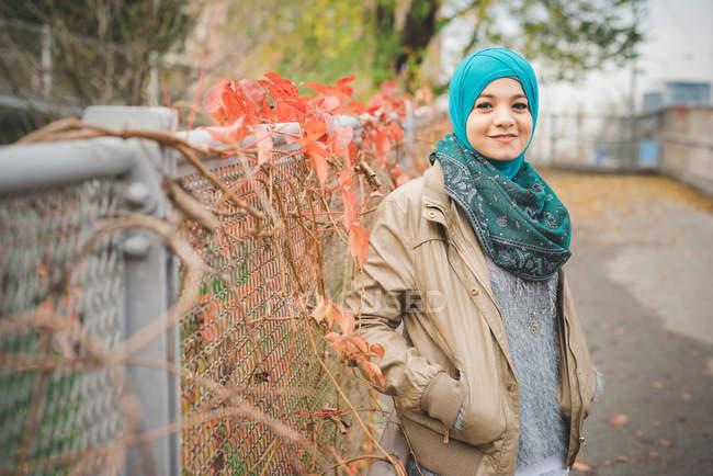 Retrato de mujer joven con las manos en el bolsillo en el camino del parque - foto de stock