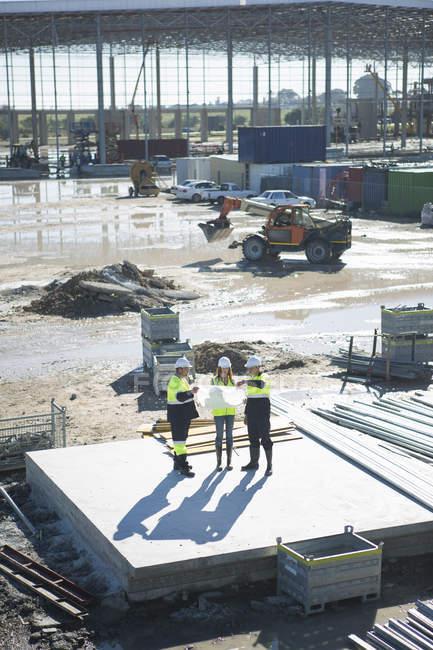 Высокий угол обзора архитекторов и управляющего площадкой, глядя на чертеж строительной площадки — стоковое фото