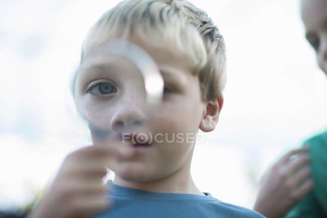 Портрет мальчика с лупой на глазах — стоковое фото