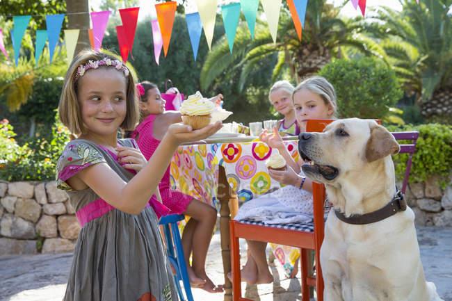 Ragazza alla festa di compleanno con cane che tiene cupcake — Foto stock