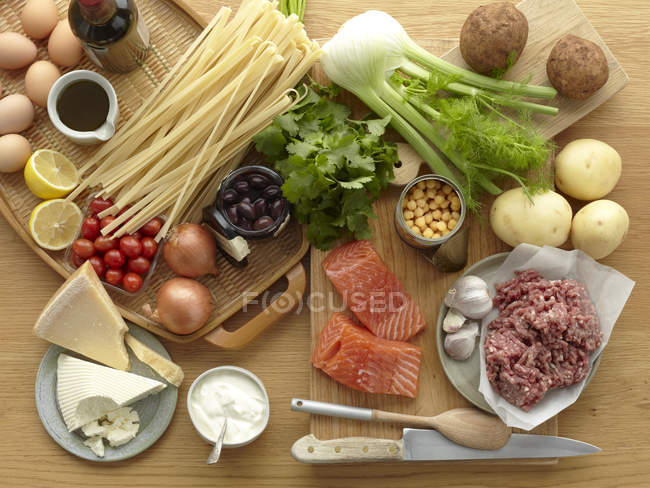 Fresh raw foods with eggs, pasta, herbs, cheese, vegetables, salmon and minced pork — Stock Photo