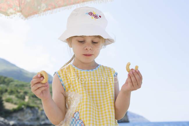 Дівчата носіння sunhat їдять кільцева на пляжі — стокове фото