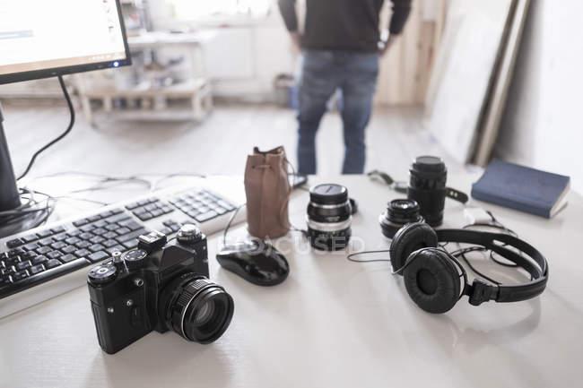 Камера с аксессуарами на столе с фотографом-мужчиной на заднем плане — стоковое фото