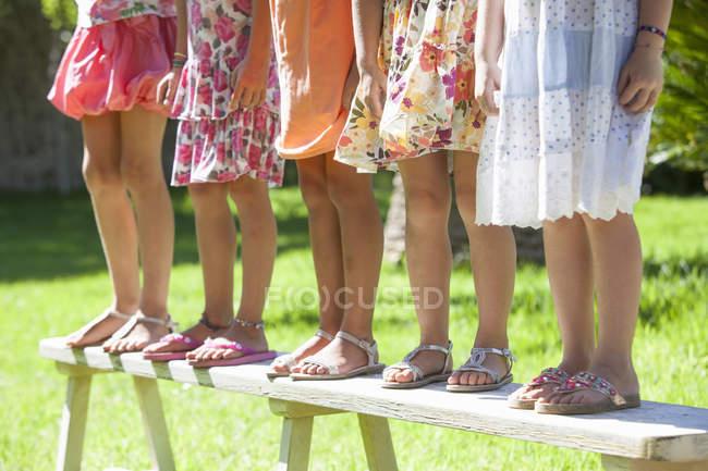 Обрезанный снимок ног пяти девушек, стоящих на скамейке в саду — стоковое фото