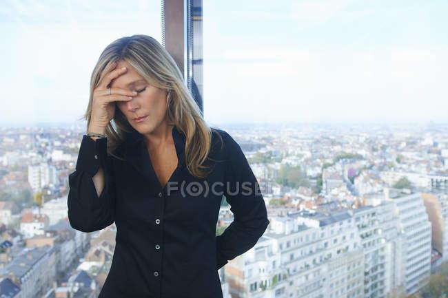 Стрессовая деловая женщина перед окном офиса с Брюсселем, Бельгия — стоковое фото