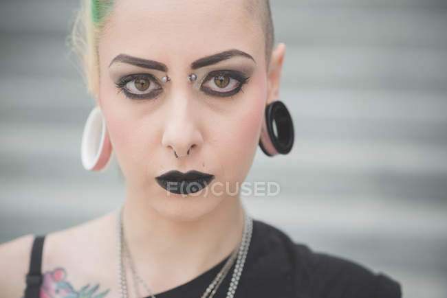 Portrait of young female punk with nose and earlobe piercings — Stock Photo