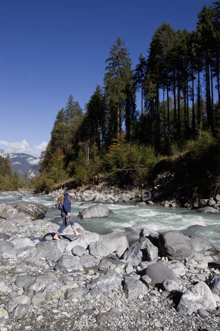 Randonneur pédestre sur des rochers fluviaux, Grindelwald, Suisse — Photo de stock