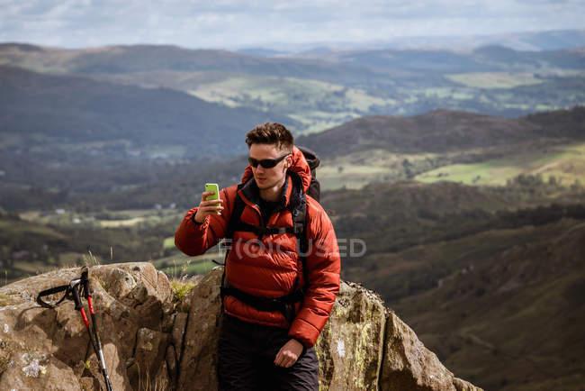 Joven excursionista masculino tomando selfie smartphone de montaña, El Distrito de los Lagos, Cumbria, Reino Unido - foto de stock