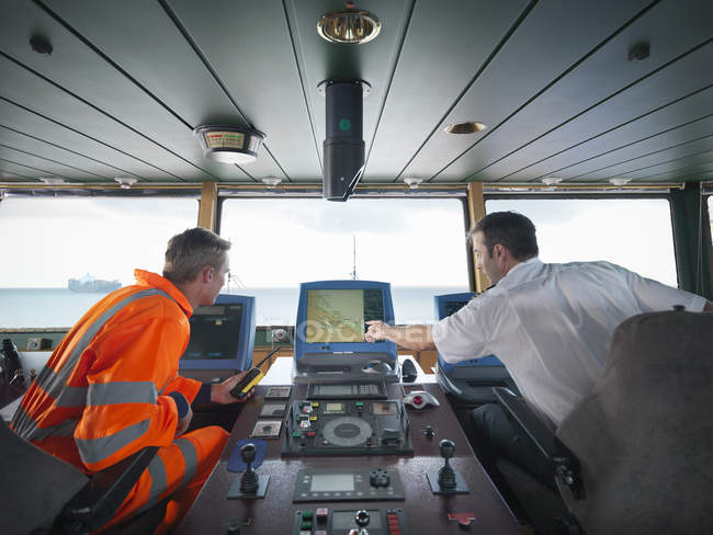 Ship worker and captain inspecting radar on ship at sea — Stock Photo